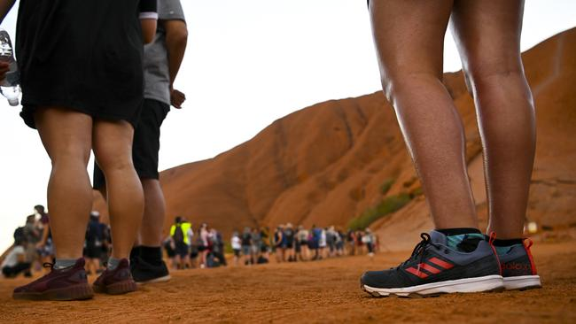 Tourists are seen lining up to climb Uluru, also known as Ayers Rock at Uluru-Kata Tjuta National Park in the Northern Territory. Picture: AAP/Lukas Coch