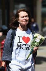 A woman makes her way to lay flowers in St Ann Square on Tuesday, May 23, 2017 in Manchester,England. Picture: Getty