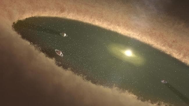 An artist's impression of planets forming in a transition disc-like LkCa 15. The planets within the disc sweep up material that would have otherwise fallen onto the star. Picture: NASA/JPL-Caltech