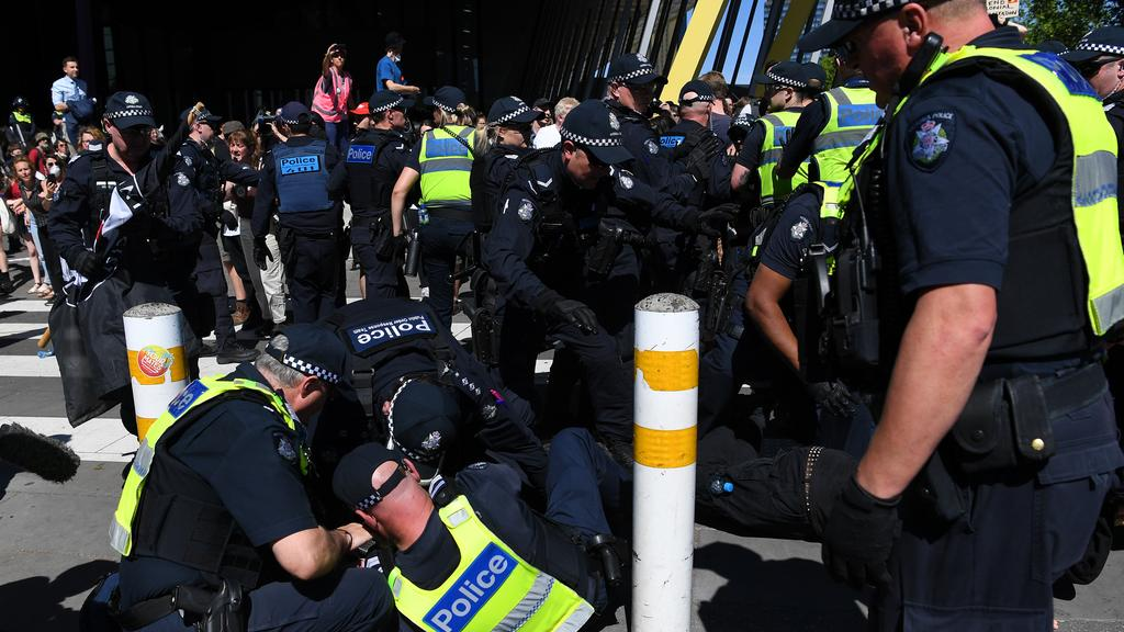 Police officers fall to the ground after a clash with protesters. Picture: AAP Image / James Ross