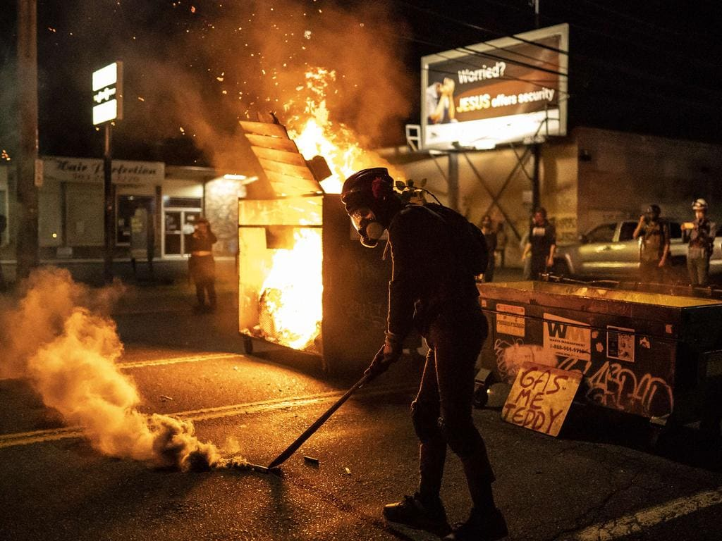 A protester walks past a dumpster fire. Picture: Nathan Howard