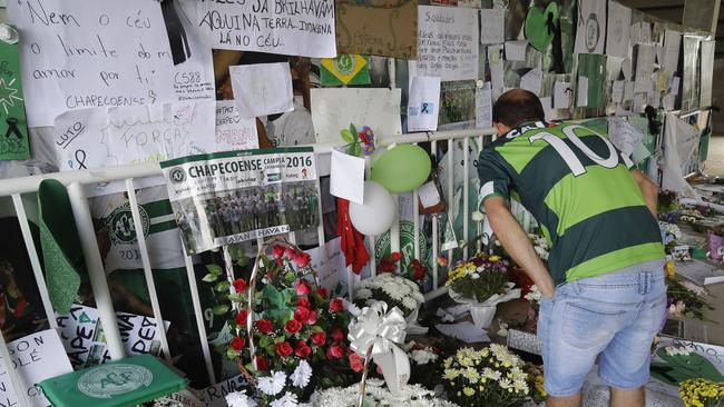 A fan of the Chapecoense soccer team reads messages