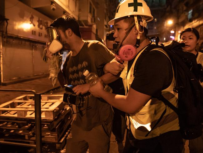 A medic carries a protester away after police fired teargas during a demonstration on Hungry Ghost Festival day outside a police station in Sham Shui Po district. Picture: Getty