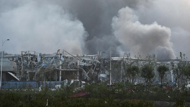 Charred ruins ... Smoke billows from the site of an explosion in Tianjin. Picture: AFP Photo/Greg Baker