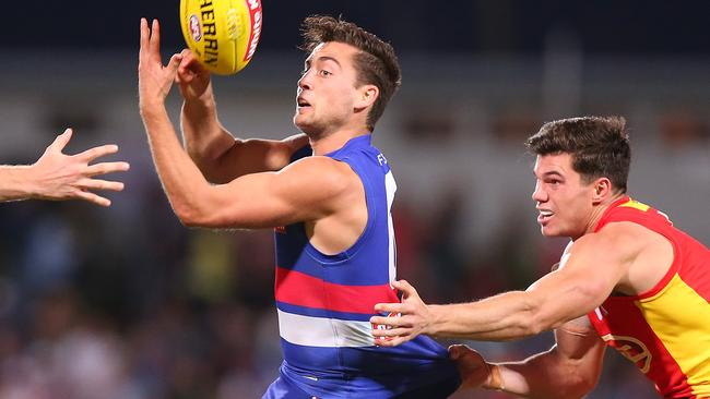 Luke Dahlhaus gets his handball away as Jaeger O'Meara tackles him.