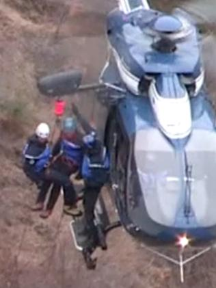 Deployed ... search and rescue personnel being lowered close to the crash site. Picture: AFP