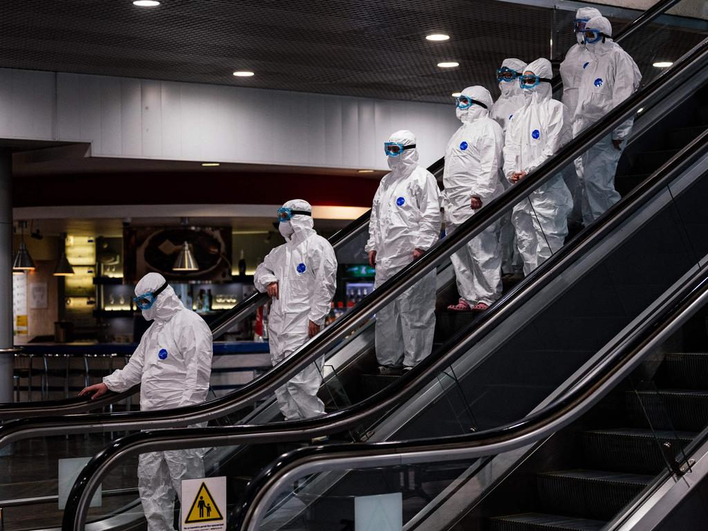 Medical staff wearing protective suits ride an escalator at Moscow's Sheremetyevo airport on March 18. Picture: Dimitar Dilkoff/AFP