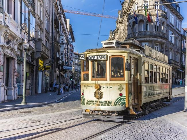 Porto, Portugal - April 24, 2016: Electric tram going past in Porto city centre, Portugal. Buildings and historic architecture in the old city centre. Many tourists in this city at the Ribeira district, near the Douro riverside. Photo: iStock