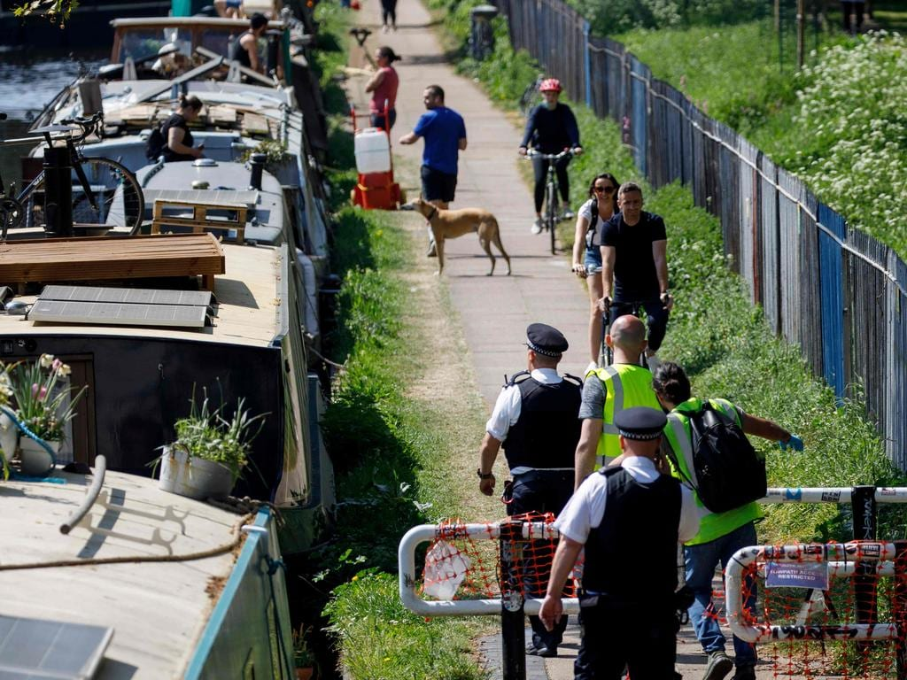 Police officers patrol along the Hertford Union Canal in east London. Picture: AFP