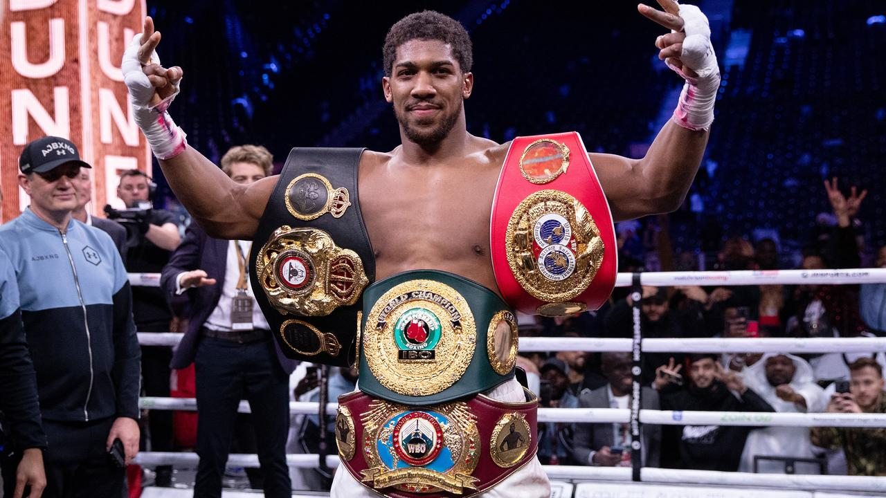 Anthony Joshua poses for a photo with the IBF, WBA, WBO & IBO World Heavyweight Title belts.