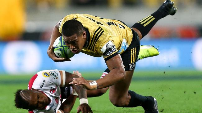 Julian Savea of the Hurricanes is tackled by Elton Jantjies of the Lions.