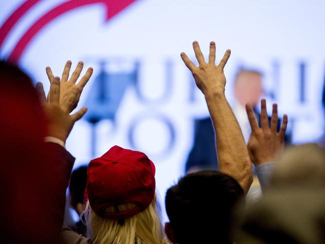 "Members of the audience hold up four fingers and chant ""Four More Years"" as President Donald Trump, speaks at the Turning Point USA Teen Student Action Summit. Picture: AP"