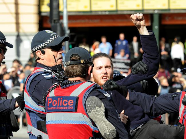 Police move in to remove vegan protesters from Flinders and Swanston streets. Picture: Andrew Henshaw