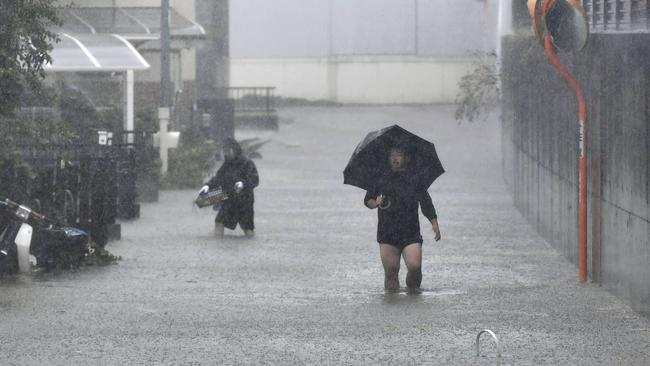 People walk through a flooded street affected by Typhoon Hagibis, in Shizuoka, central Japan. Picture: Kyodo News via AP