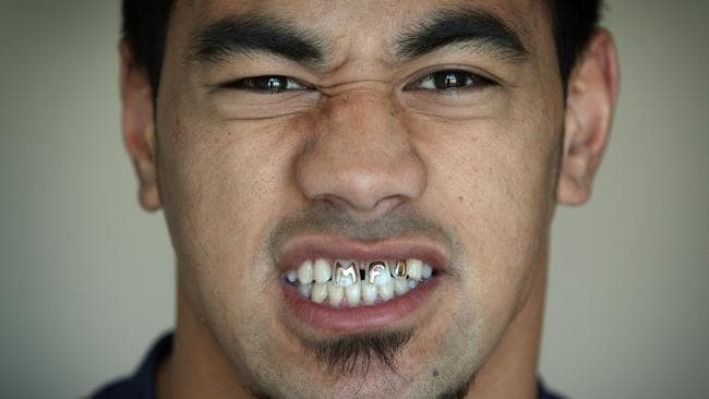 Mahe Fonua flashes his golden initials in his front teeth.
