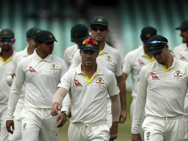 David Warner (C) leaves the field with teammates following Australia's victory.