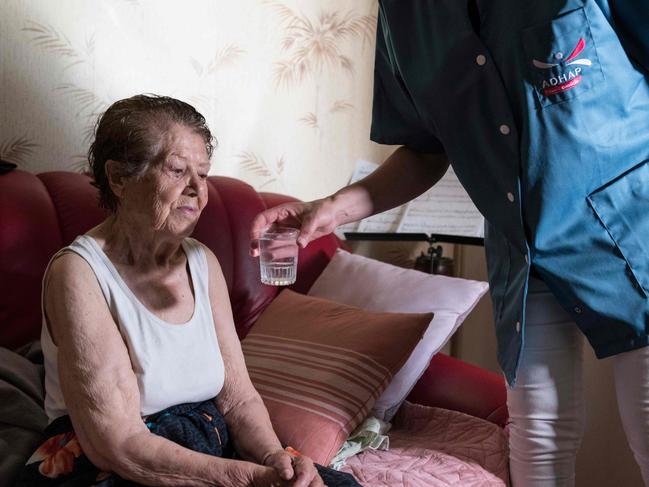 Apersonal care assistant gives a glass of water to an elderly person as she visits her house to help her to avoid heatstroke and dehydration during the heatwave. Picture: Thierry Zoccolan / AFP