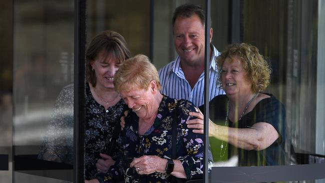 Angela Gore (centre) the wife of Bernard Gore, and son Mark leave the inquest on Tuesday. The family were briefly stuck in the revolving door, sharing a laugh after another day of heartbreak. Picture: Dan Himbrechts/AAP