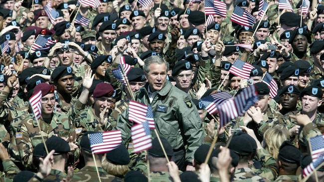 US President George W. Bush wades through a crowd of American troops waving flags, at Fort Campbell, Kentucky in 2004.
