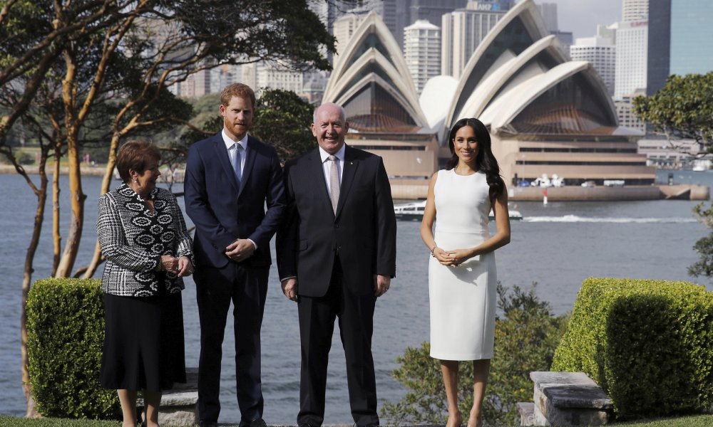 The Duke and Duchess of Sussex, Australia's Governor General Peter Cosgrove and his wife Lynne Cosgrove stand in the grounds of Admiralty House in Sydney, with a view of the Sydney Opera House, on the first day of the royal couple's visit to Australia Tuesday, October 16, 2018. Harry and Meghan will take part in 76 engagements in Australia, Fiji, Tonga and New Zealand over their 16-day trip to the Pacific region. (Phil Noble/PA via AP)