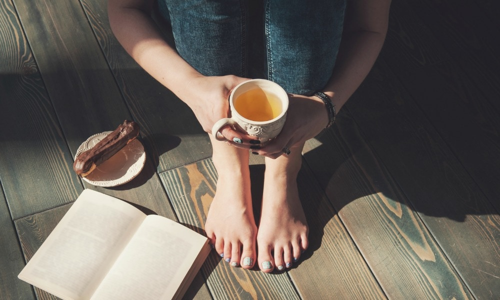 Cozy photo of young woman with cup of tea sitting on the floor in sunlight