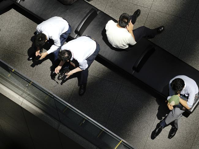 People rest in shade of a building in Tokyo. Picture: AP