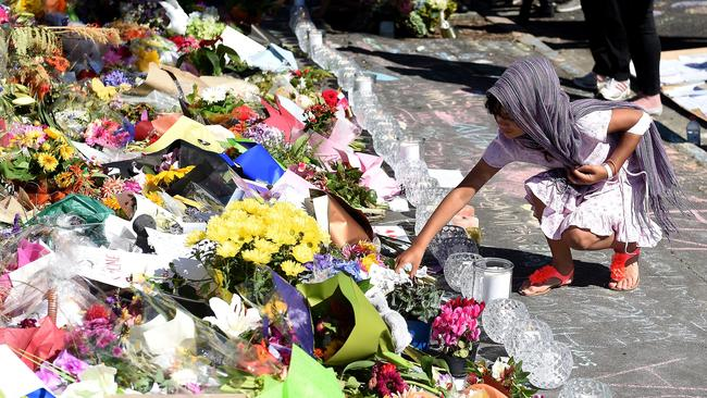 A young girl lays flowers outside Al Huda mosque at Dunedin, New Zealand on Saturday. Picture: Joe Allison/Allison Images/news.com.au