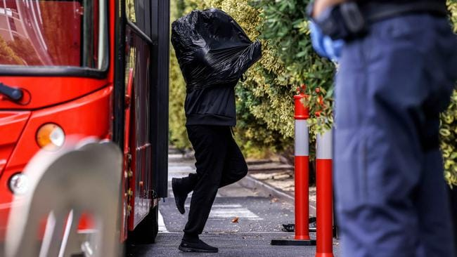 A person from Melbourne's CBD wears a garbage bag during their transfer to the Pullman Hotel in Albert Park. Picture: NCA NewsWire / Ian Currie