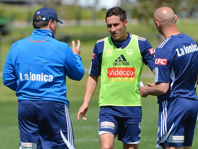 Ange Postecoglou and Kevin Muscat talk to Mark Milligan during a Melbourne Victory training session.