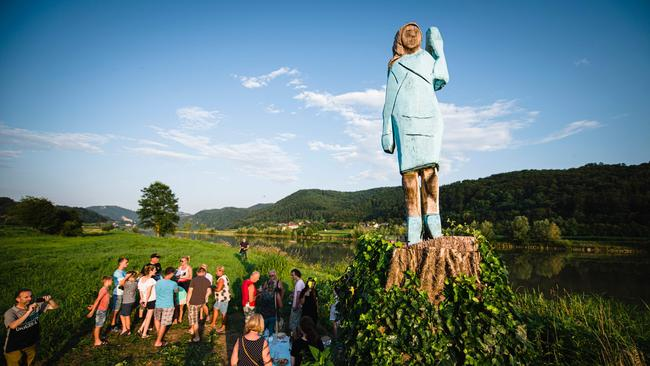 People gather around what conceptual artist Ales 'Maxi' Zupevc claims is the first ever monument of Melania Trump, set in the fields near the town of Sevnica. Picture: AFP