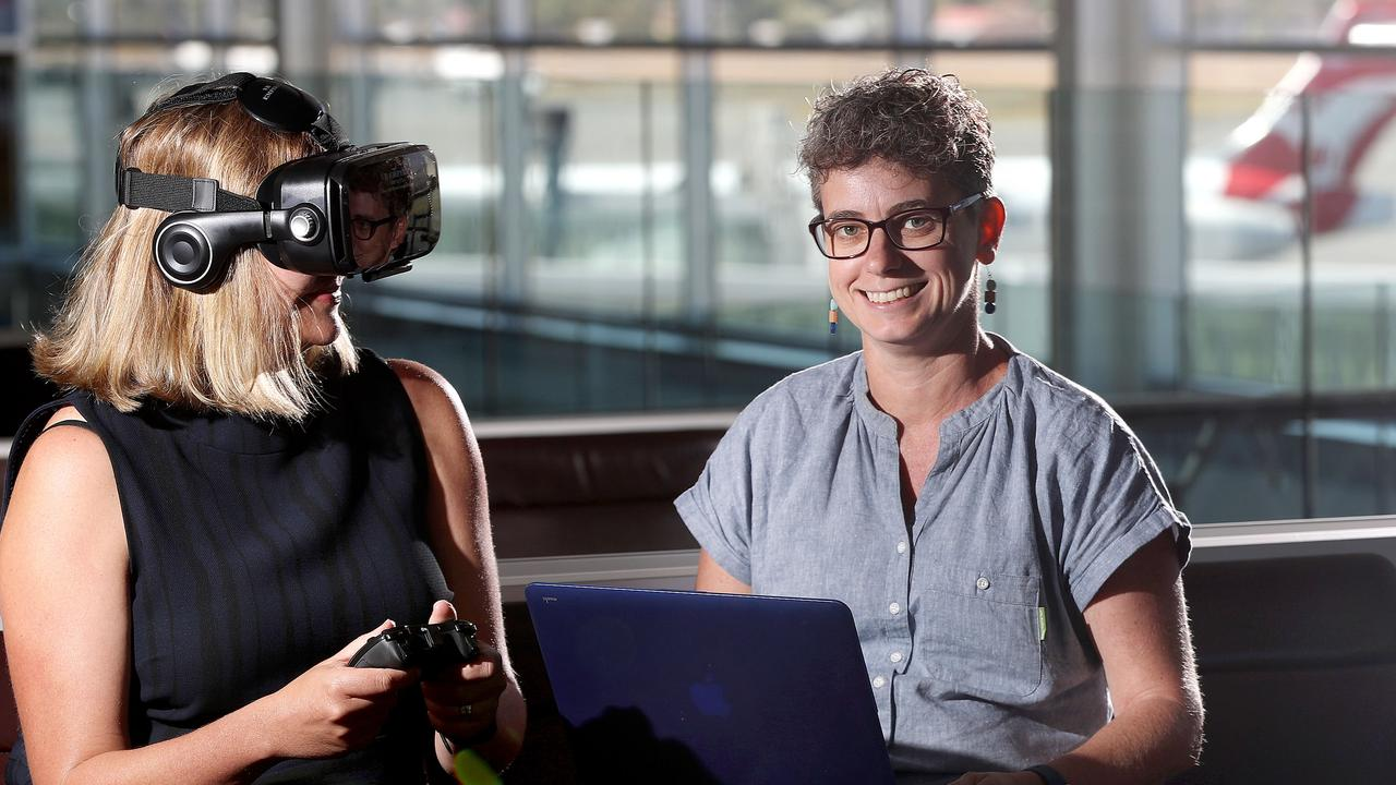 Angelique Foran and Dr Emma Johnston test out their VR goggles at the Adelaide Airport that can help people overcome their fear of flying. Picture: Calum Robertson