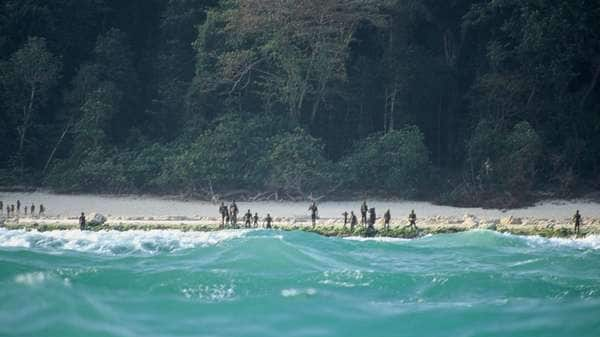 The Sentinelese stand guard on an island beach. Most contact with the tribe has been made from boats sitting just outside arrow range. Picture: Christian Caron – Creative Commons A-NC-SA