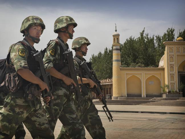 Chinese soldiers march in front of the Id Kah Mosque, China's largest. Picture: Getty
