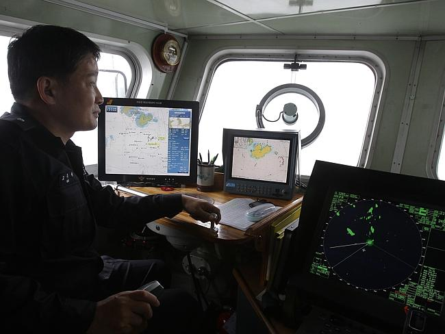 Looking for survivors ... a South Korean Coast Guard observes the site of the sunken ferry off the coast of Jindo Island. Picture: Chung Sung-Jun