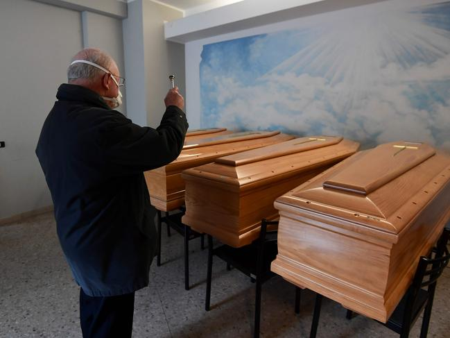 Italian priest, Don Giuseppe Locattelli, blesses coffins of the dead. Picture: AFP