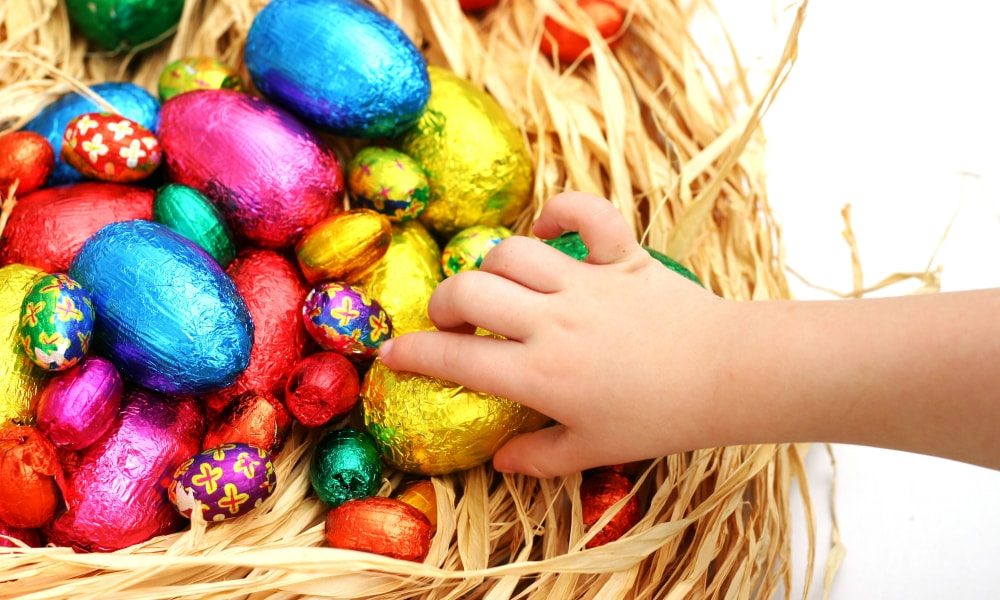 A child taking an Easter egg from a nest.