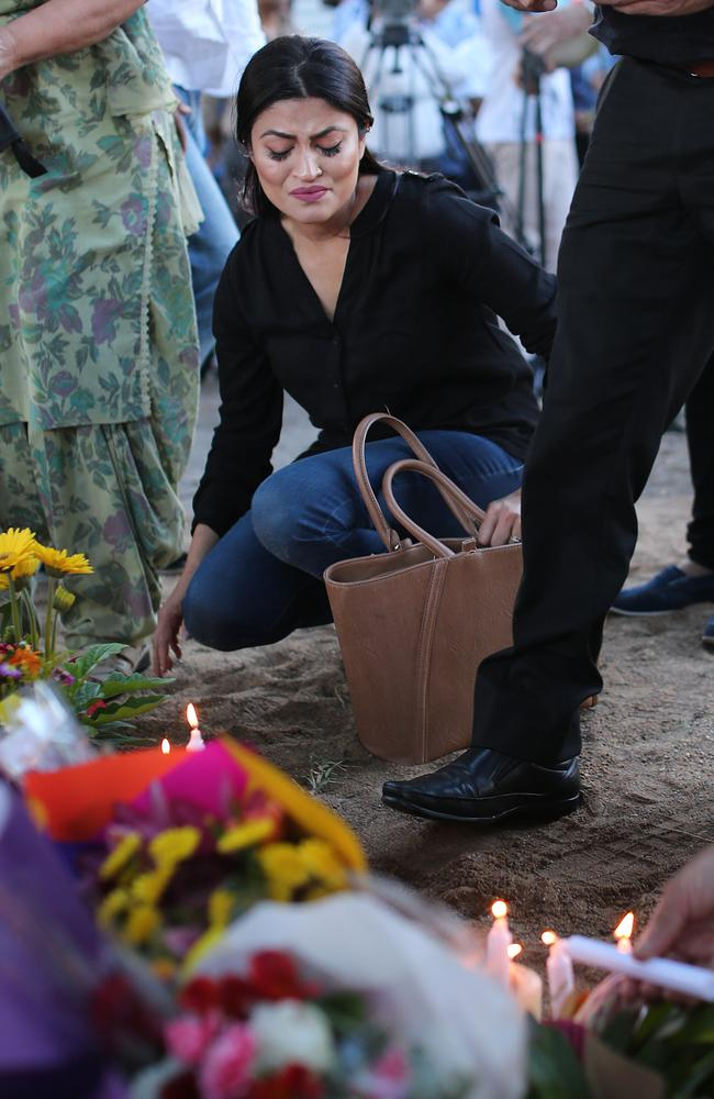 A woman weeps outside a memorial for slain Brisbane city council bus driver Manmeet Alisher in Moorooka tonight. Pictures: Jack Tran