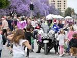 A motorcycle policeman is mobbed for High Fives. Photo Naomi Jellicoe