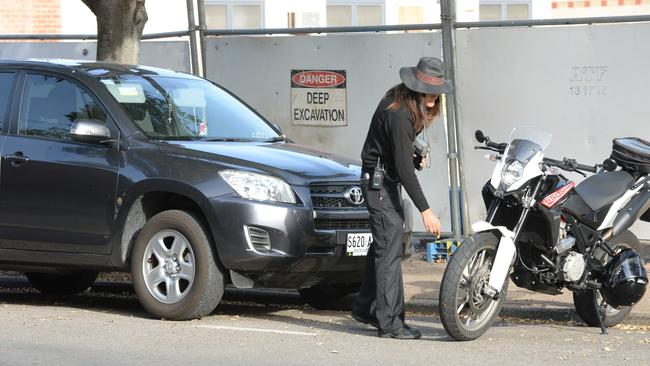 A parking inspector checks out vehicles parked in the special event, two-hour limit. Picture: David Cronin.