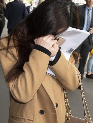 Kaiqi Chen covers her face outside the Melbourne Magistrates Court. Picture: AAP Image/Ellen Smith