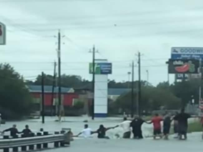 Rescuers form a human chain to reach the stranded man. Picture: Storyful