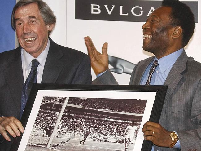 Brazilian soccer legend Pele, right, presents former England goalkeeper Gordon Banks with a photograph showing Banks saving a header from Pele in the 1970 World Cup.