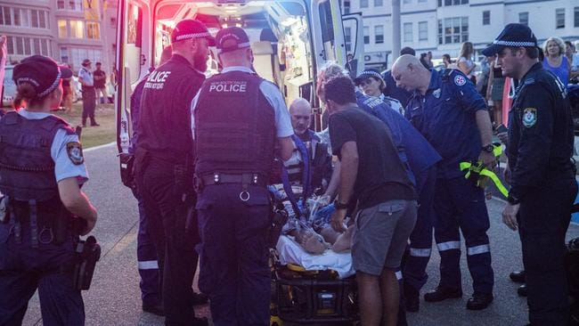 Paramedics moved the man from the beach to a waiting ambulance. Picture: Dylan Robinson