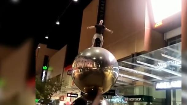 Mall's Balls Rundle Mall: Man jumps on to Spheres sculpture