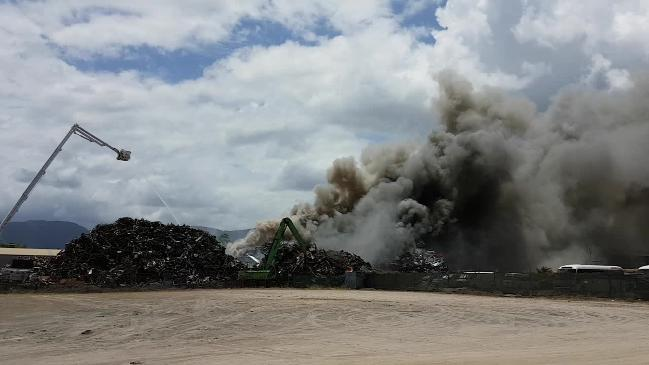 Firefighters work to put out the flames as smoke billows across Cairns from Sims Metal.
