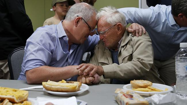 Prime Minister Scott Morrison comforts Owen Whalan, 85, at Club Taree Evacuation Centre on Sunday. Picture: AAP Image/Darren Pateman