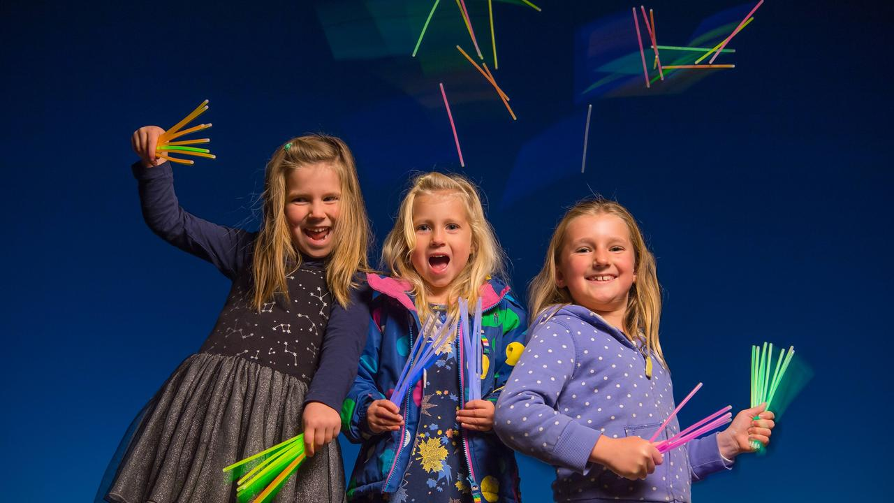 Sisters Vaiva, 5, Kira, 3 and Nina, 7 have fun with their glow sticks. Picture: Jason Edwards