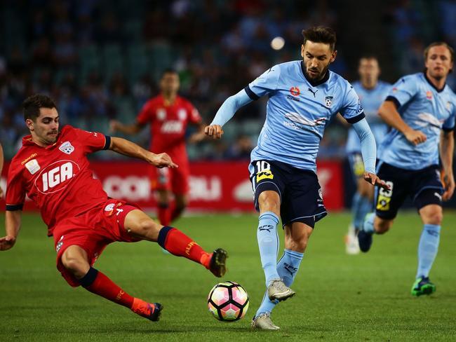 Milos Ninkovic of Sydney FC is tackled by Ben Garuccio of United.