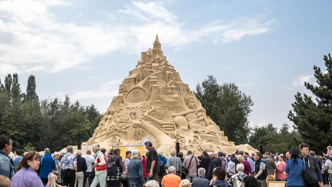 Visitors stand near the huge sandcastle. Picture: Maja Hitij