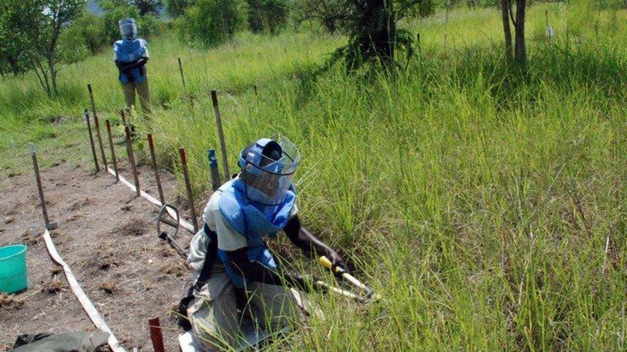 TO GO WITH AFP STORY BY PETER MARTELL A Southern Sudanese female deminer clears grass and soil around a suspected landmine in the minefield of Bungu, in Central Equatoria state, south Sudan, on June 24, 2009. The all-female team, working for Norwegian People's Aid (NPA), are helping clear the legacy of Sudan's 22-year civil war. AFP PHOTO/PETER MARTELL